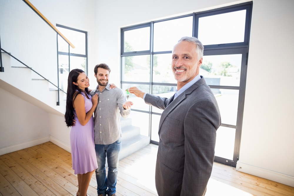 agent giving couple the keys to their new home