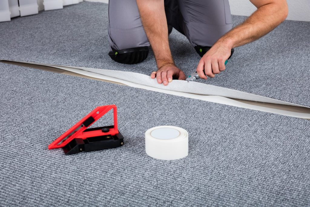 Worker using an adhesive tape for the carpet