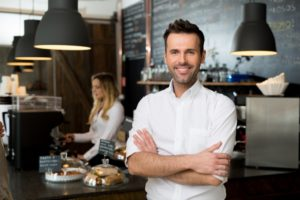 small business owner standing with crossed arms with employee in background preparing coffee
