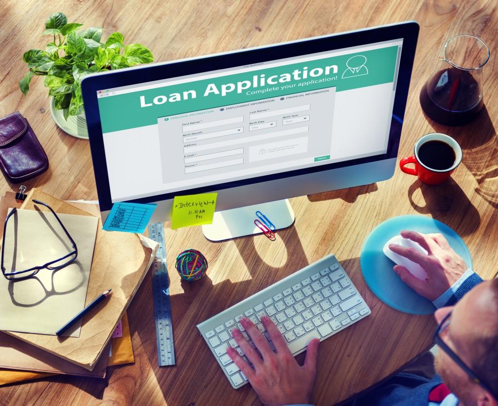 man filling up a loan application form online