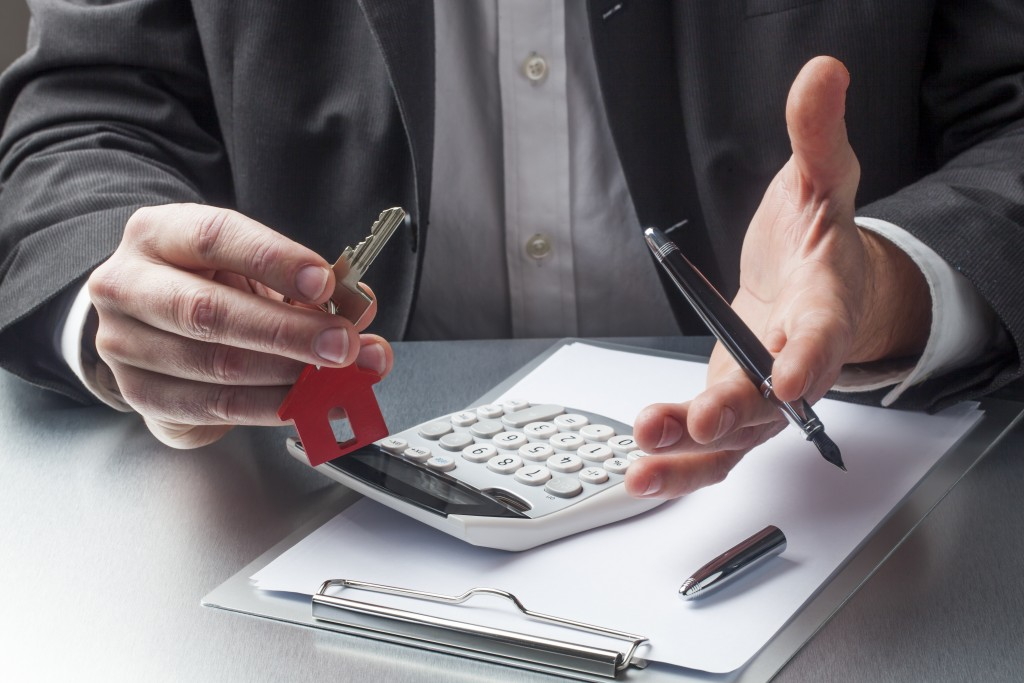 Agent holding house key with contract and calculator