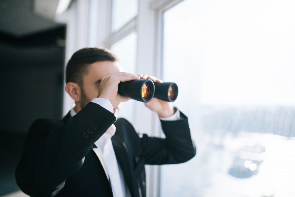 Businessman with binoculars spying on competitors or looking for oppportunities
