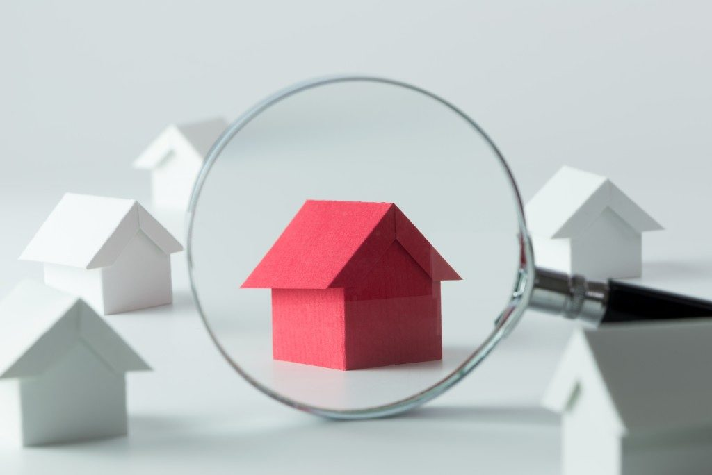 magnifying glass on a red miniature house
