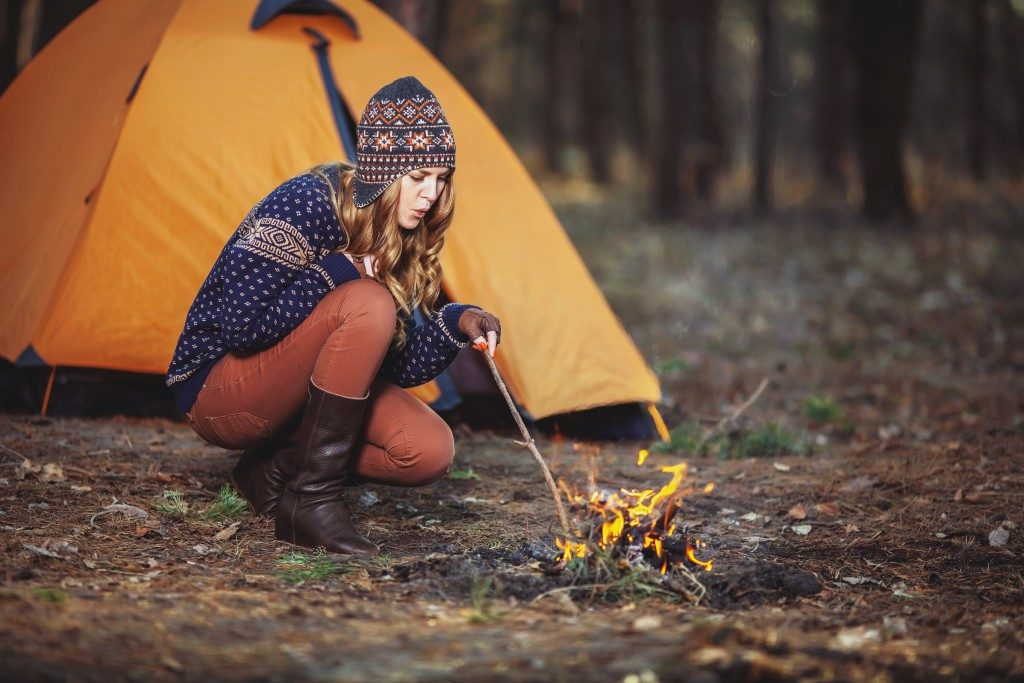 woman starting a fire in the woods