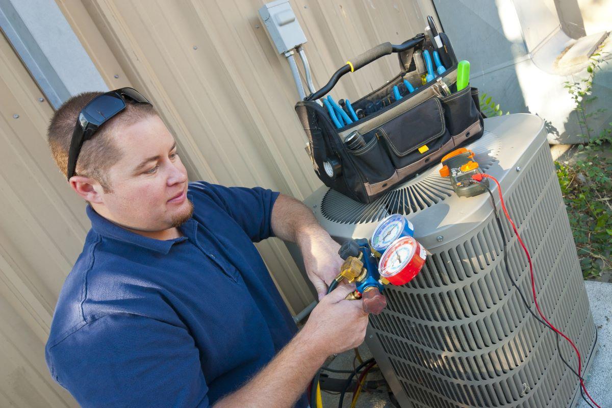 man maintaining air conditioning unit