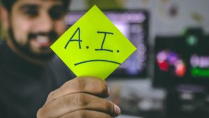 man holding out a sticky note with AI written on it