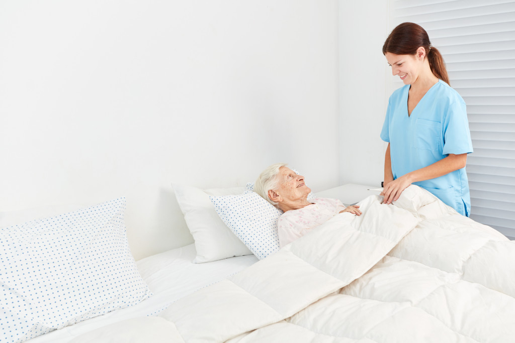 nurse taking care of old woman