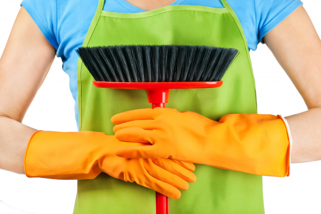 holding a broom with cleaning gloves