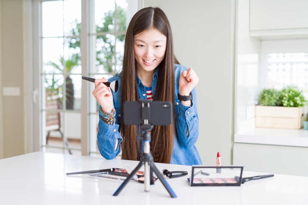 girl broadcasting using her mobile phone on a phone stand
